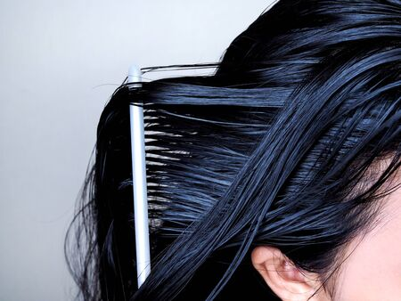 Hair and scalp health care By combing black hair and long on head with white comb. Imagens - 131296578