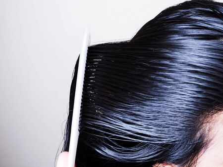 Hair and scalp health care By combing black hair and long on head with white comb.