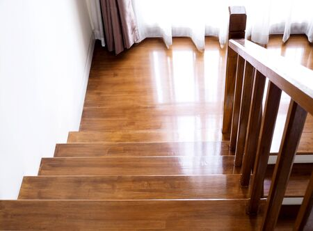 Wooden stair in house, way down stairs with windows and curtains.
