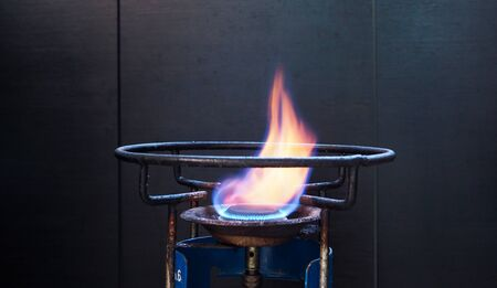 Close-up of fire on stove top with old and rusty gas stove, placed in thai kitchen to cook with dark black background.