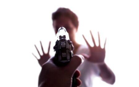 close-up of gun in hand with aiming at women, scared and shocked. Blur focus on Asian body 스톡 콘텐츠