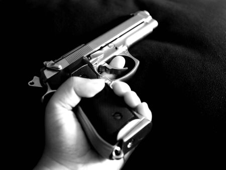 Hand blurred with focus selection of gun on black background. close-up of finger at trigger. 스톡 콘텐츠