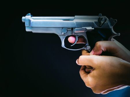 Hand with aiming gun on black background. 스톡 콘텐츠