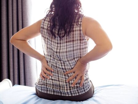 woman with back pain and waist pain Symptoms from muscle inflammation And hard work, office syndrome Stock Photo