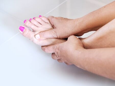 Young asian woman massaging on feet to relax muscle of foot pain, soles, heels and toe from foot injury or pain from disease.