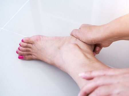 Asian women with tendon inflammation, muscles and nerves on feet, Heel pain and use hand massage to relieve.