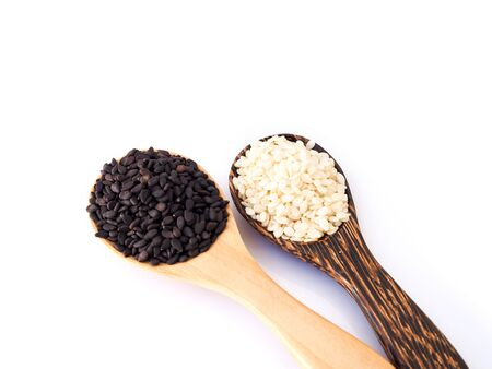 White sesame seeds and black sesame seeds in wooden spoon isolated on white background. Stock fotó