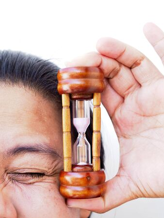 Close-up face of Asian woman with hand holding hourglass, Time to take care of skin and wrinkles.
