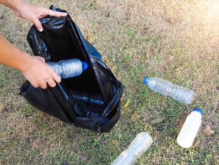 Preserving and cleaning environment collect plastic water bottles to recycle with black bag.