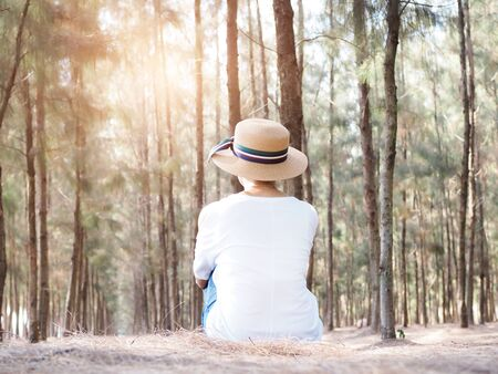lifestyle of middle-aged thai asian woman wearing straw hat sitting and relax in brown pine forest.