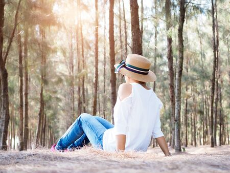 Thai women sitting with relaxation in pine forest, travel with happiness and slow life concept.