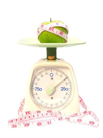 Green apples and tape measure on weight scale isolated on white background