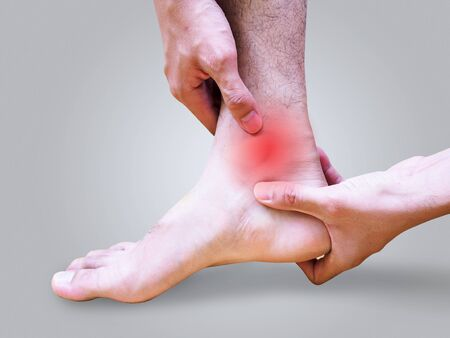 Young man suffering foot and ankle pain or sprained ankle.