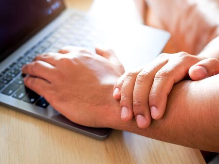 Asian Businessman people suffer from wrist pain hand and arm pain from working with laptop computer.