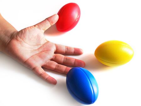 hand and stress balls colored yellow, red, blue, squeeze ball for hand exercise. isolated on white background. Stock Photo