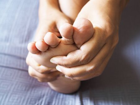 Asian women use hands massage on toes with numbness nerves and foot pain.