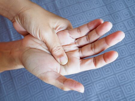 Woman suffering with hand pain and palms, beriberi symptom on hand nerves or inflammation of the muscles from work.