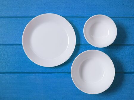 Top view of white ceramic plate or round dish, bowl and crockery on blue wooden table. Stock Photo