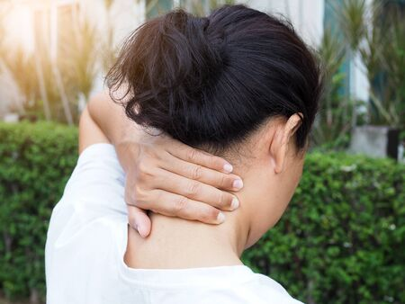 Thai Asian women with body aches, using hands massage on neck to relieve pain.
