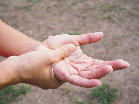 Close up of hand massage on palms to relift ache, hand pain and numb. Stock Photo