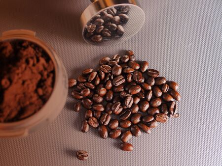 Top view of brown dark coffee powder and coffee beans.