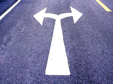 White arrow sign on asphalt road, Turn left and right signs on the road junction. Standard-Bild - 147828974