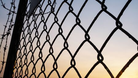 silhouette on a metal mesh fence and barbed wire. Safety and freedom.
