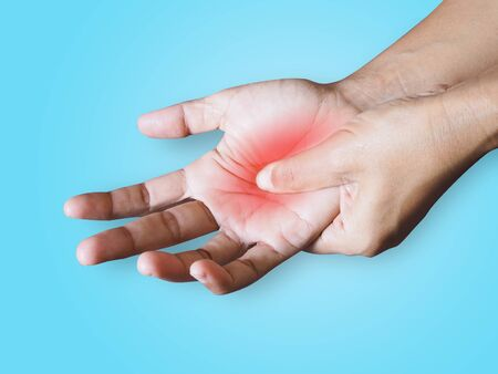 Injury with hand pain isolated on blue background with clipping path.