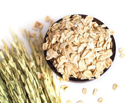 Top view of dried oatmeal, rolled oats in wooden bowl with dry grains and ear of rice isolated on white background.