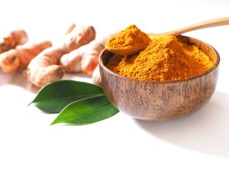 Above of turmeric powder, curcuma in wooden bowl isolated on white background.