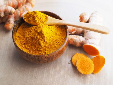 Top view of turmeric powder, curcuma and turmeric root sliced on wooden table background.