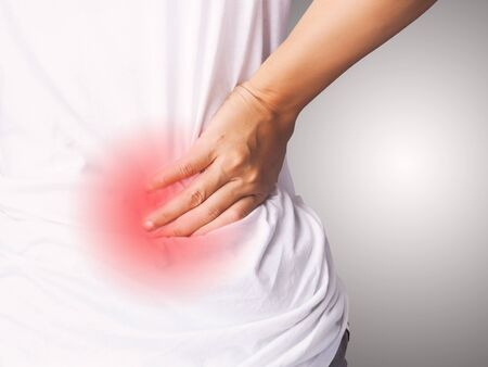 Thai asian woman with lumbar pain, backache and massage on waist to pain relief.