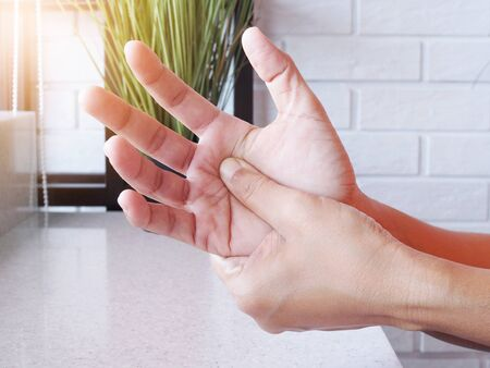 Close-up of women hand with massage hands, fingers and palm from pain and numbness, Exercise and massage to relieve hand pain. Stock Photo