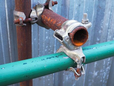 Old rusted steel pipe and couplings, steel rings lock pipe and screw bolt with galvanized sheet background.