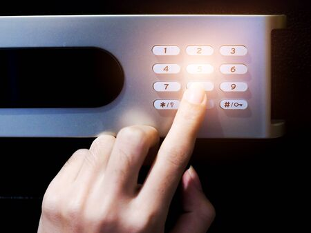Close-up of hand pressing numbers with password code of lock on safe box.