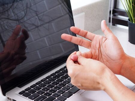 Close-up of hands and fingers with pain and inflammation from work with notebook computer. Stock Photo