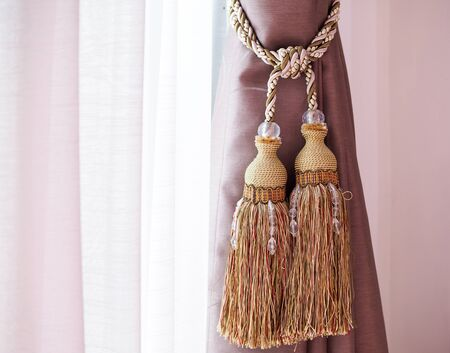 Brown curtain with rope tassel and sheer curtains.