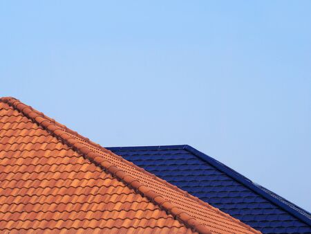 On top roof of house from clay tiles of Asian building with blue sky is background.