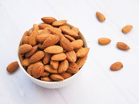 Top view of almond seeds in white bowl isolated on white background.