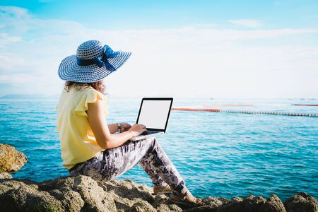 Business woman sitting by the sea with laptop computer Archivio Fotografico