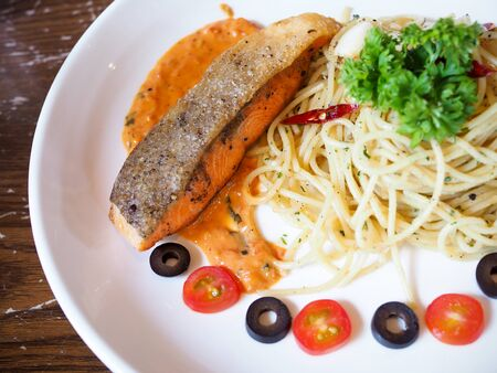 Food with spaghetti and salmon steak in white ceramic plate on table.