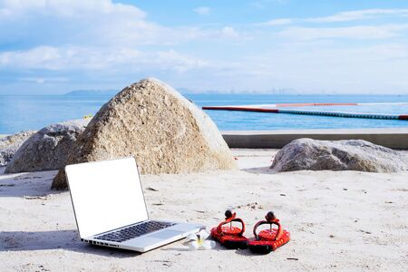 Laptop computer and shoes on the beach. work and travel in summer. 스톡 콘텐츠