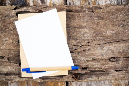 Note paper and pen placed on old wooden boards and decayed. The texture of the large brown wood surface. concept for background.