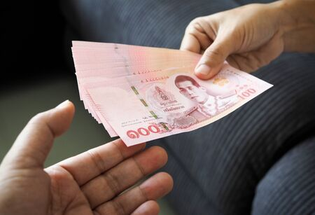 submitting Thai baht banknote money of thailand to hand that is waiting receive, Payment, bribery or sharing concept.