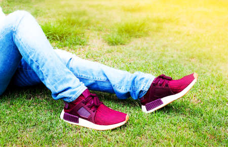 Legs of women wearing blue fashion jeans and red sneakers, sitting on a park.