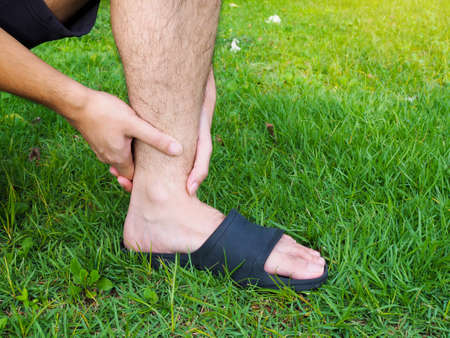 man people acute with ankle sprain with walking in garden and feeling bad.