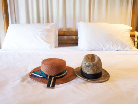 Vintage straw hat, fashion of tourist to travel put on the bed with pillow Stock Photo