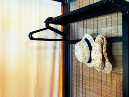 decorate the room with vintage straw hats hanging on black wooden furniture. 写真素材