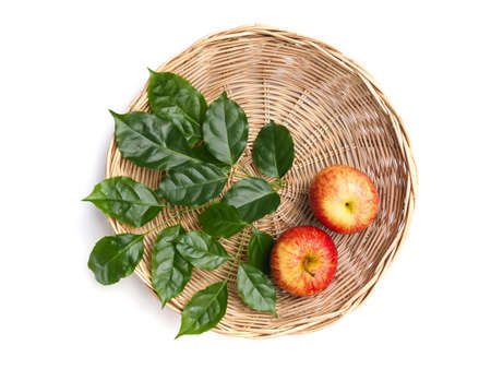 Top view of Red fruit apples in bamboo baskets and green leaves isolated on white background with clipping path