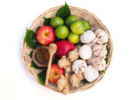 Top view of Fruits and vegetables set in bamboo basket with honey Healthy food on hand isolated on white background